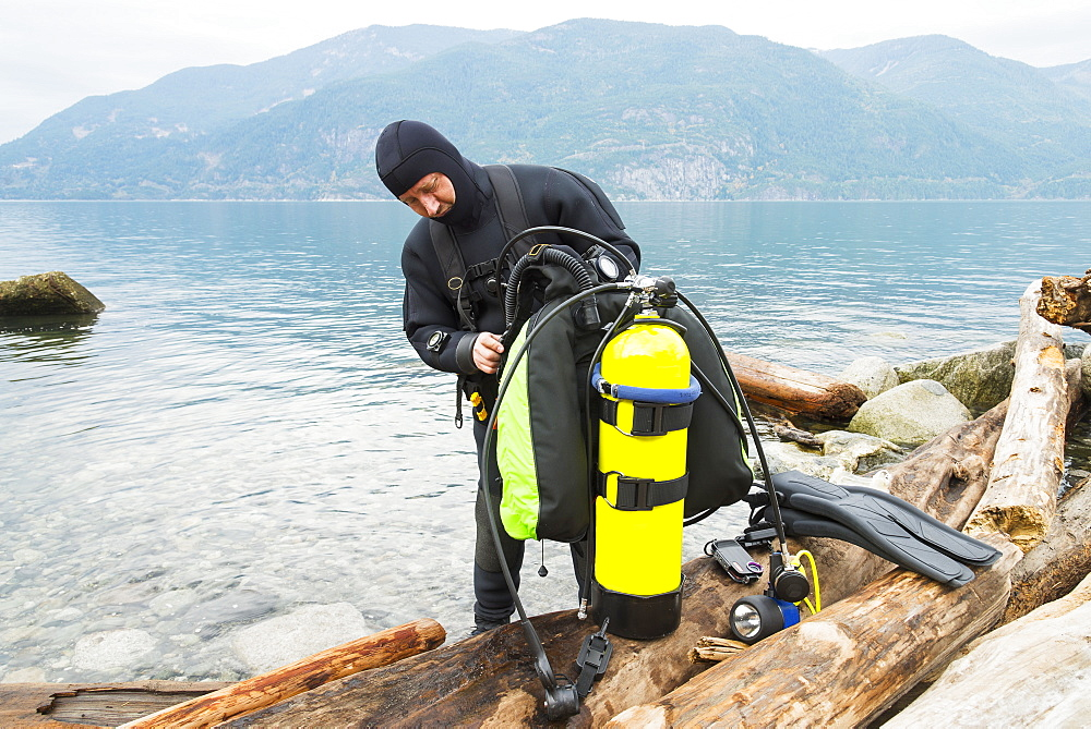 A Scuba Diver Prepares His Equipment Before Making A Dive, Britannia Beach, Howe Sound, British Columbia, Canada