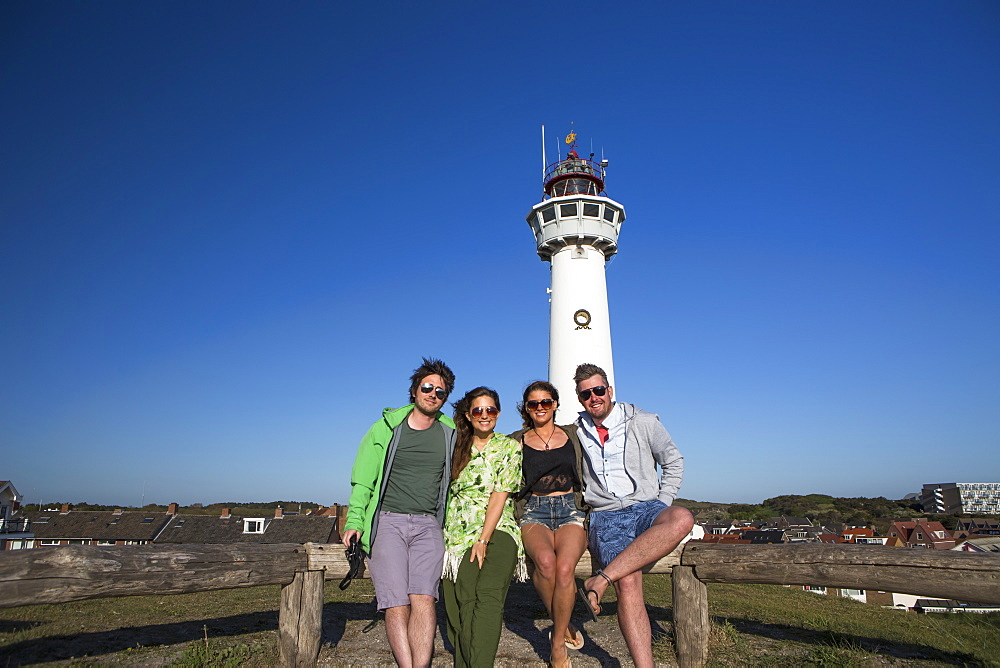 A Group Of Friends Standing With A Lighthouse In The Background Outside Of Amsterdam Central, Egmond Aan Zee, Holland