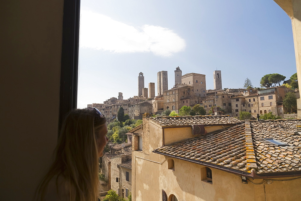 A Female Tourist Looks Out The Window At The Walled Medieval Village Of San Gimignano, San Gimignano, Province Of Siena, Tuscany, Italy