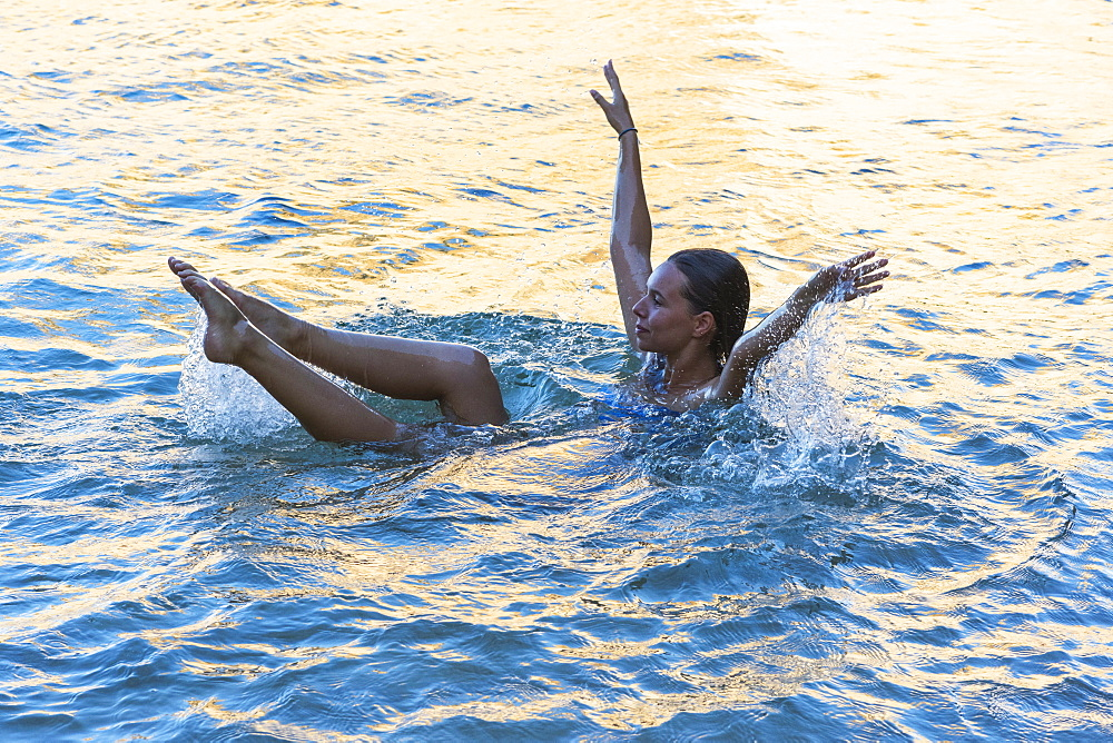 A Young Woman In The Water With Her Torso Immersed And Her Arms And Legs Above The Water, Exercising, Tarifa, Cadiz, Andalusia, Spain