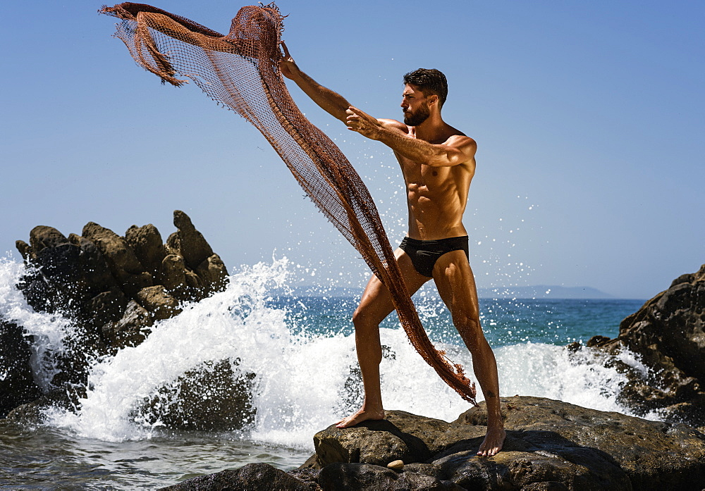 A Muscular Man In A Bathing Suit Throwing A Net Into The Water While Standing On A Rock At The Coast, Tarifa, Cadiz, Andalusia, Spain