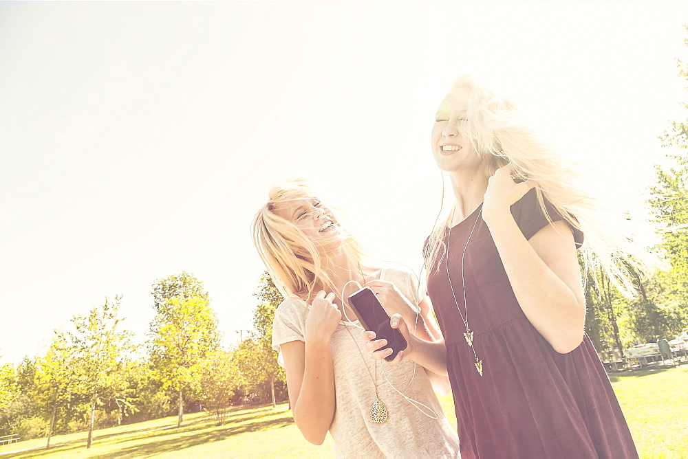 Two Sisters Having Fun Outdoors And Singing Together In A City Park While Listening To Music On An Mp-3 Player, Edmonton, Alberta, Canada