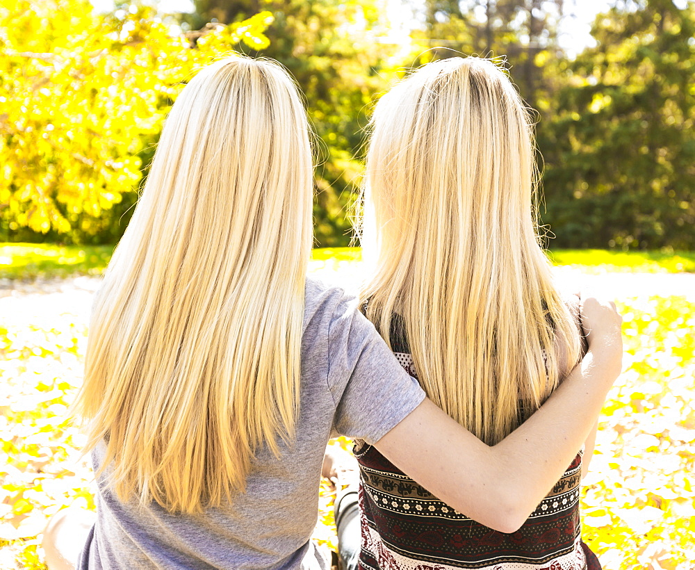 View From Behind Of Two Sisters Hanging Out In A City Park Together In Autumn, Edmonton, Alberta, Canada