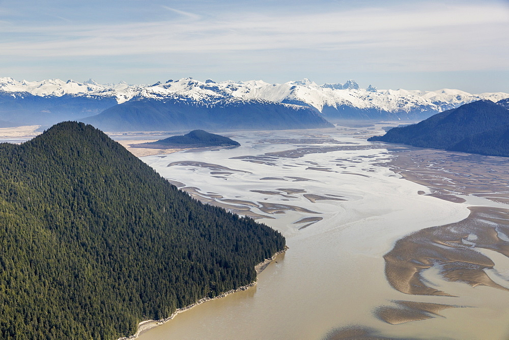 Aerial View Of Woronkofski Island Along The Stikine River Delta, Low Tide Revealing Mud Flats Below The Snow Capped Peaks In The Background, Wrangell, Alaska, United States Of America