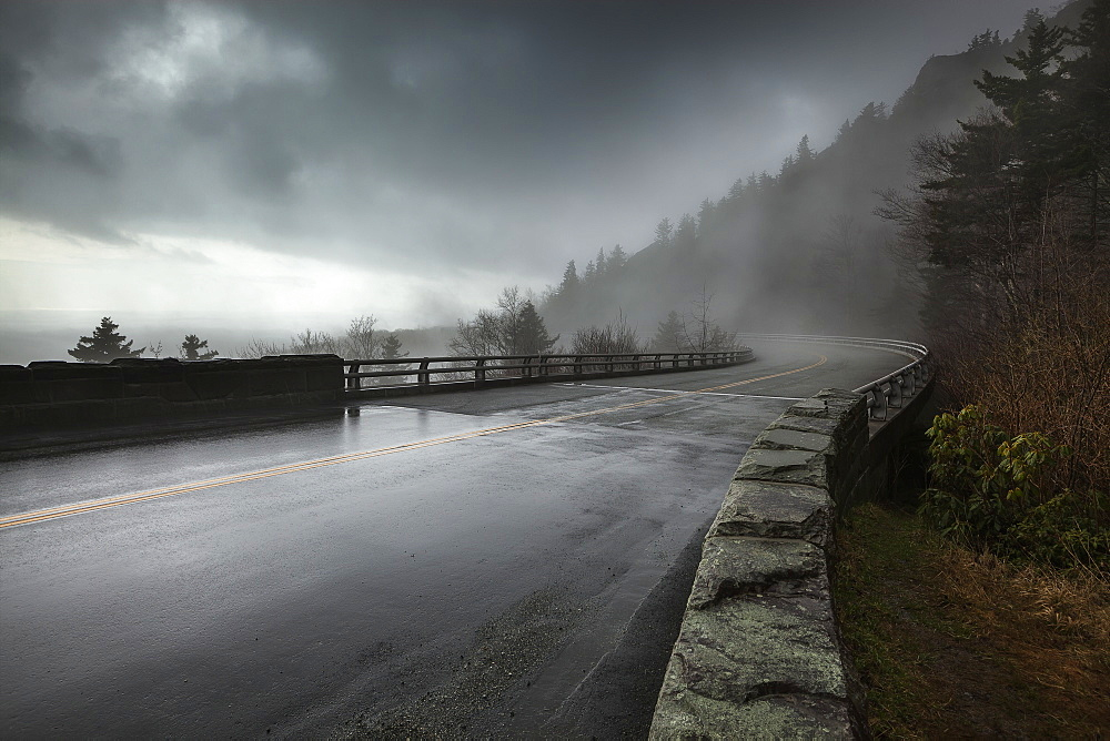 Rain On A Wet Bridge Of North Carolina's Linn Cove Viaduct On The Blue Ridge Parkway With Moody, Low-Hanging Storm Clouds And Mist, North Carolina, United States Of America