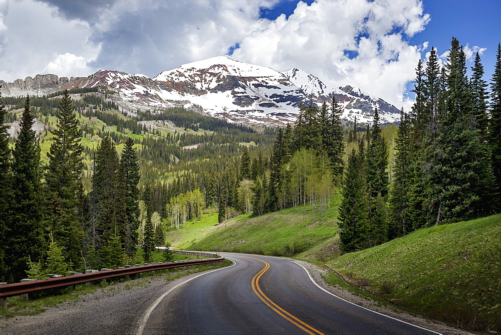 Snowcapped Rocky Mountains In The Background With A Winding Mountain Road Stretching Into The Distance, Colorado, United States Of America