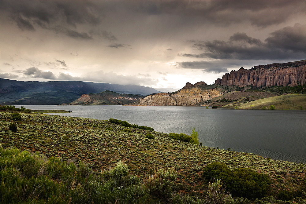 The Water And Rock Cliffs Of Blue Mesa Reservoir With Moody Clouds And Interesting Light, Gunnison, Colorado, United States Of America