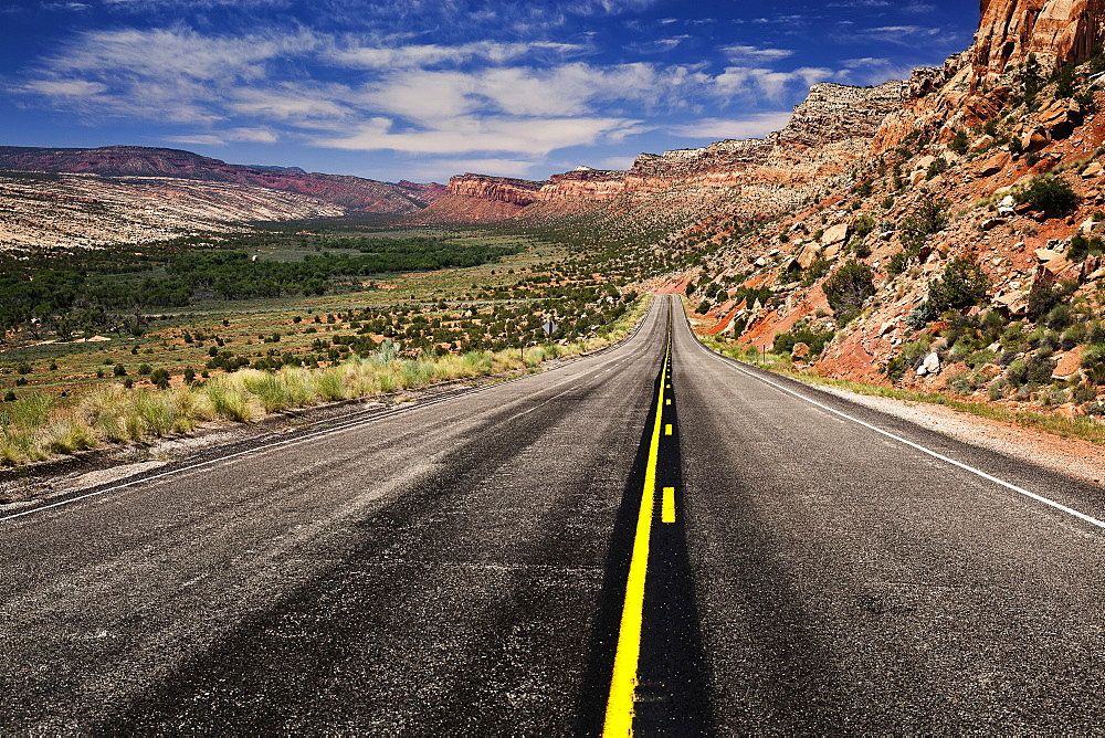 Utah Highway Stretching Into The Distance With Rock Cliffs Wrapping From The Right Side Foreground Around To The Background Center And Left Of The Photo With Blue Skies With Some Clouds, Utah, United States Of America