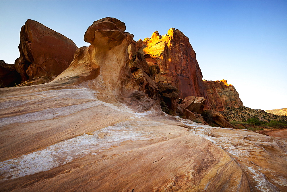 Smooth, Worn Rock Formations In The Foreground Sweeping Up To Tall Canyon Cliffs In The Background Under Clear Blue Skies, Capitol Reef National Park, Utah, United States Of America