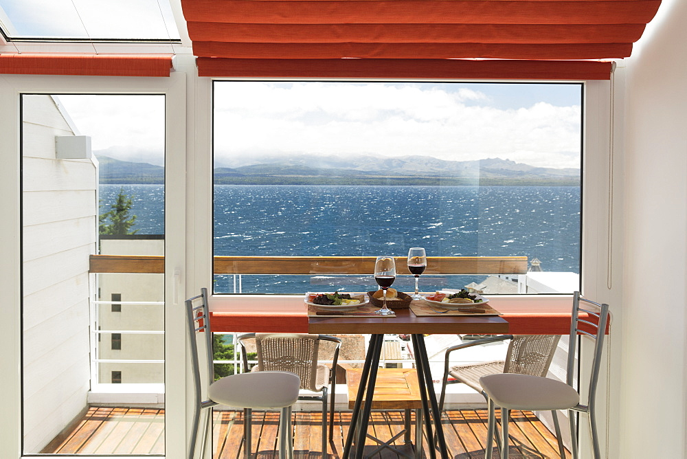 A Lunch Table With Two Glasses Of Red Wine Is Set In Front Of The Balcony Window Of A Bright Apartment With View Over A Lake, Bariloche, Argentina - 1116-45007