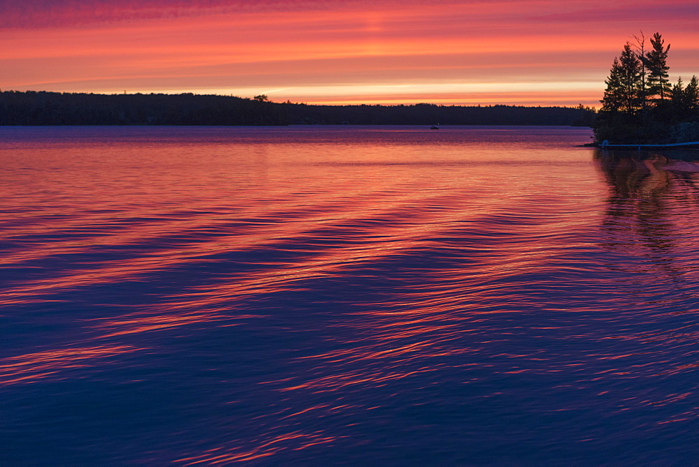 Sunset Over A Lake Reflecting Pink On The Tranquil Water, Ontario, Canada