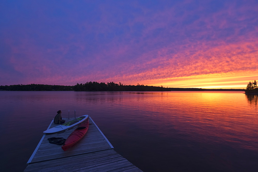 A Young Woman Sits At The End Of The Dock With Kayaks Watching The Sun Set Over A Lake, Ontario, Canada