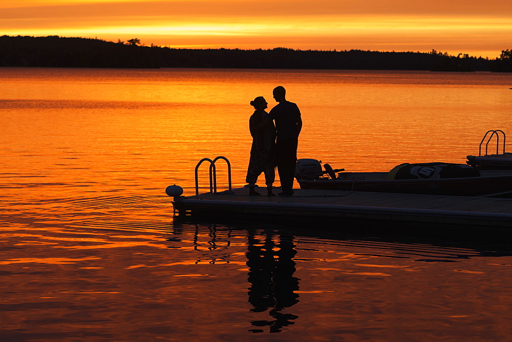 Silhouette Of A Couple Standing At The End Of A Dock At Sunset With An Orange Glow In The Sky And Reflected In The Tranquil Lake Water, Ontario, Canada