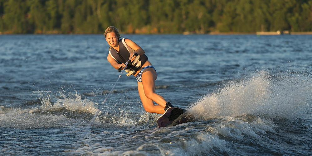 A Young Woman Wakeboarding On A Lake, Ontario, Canada