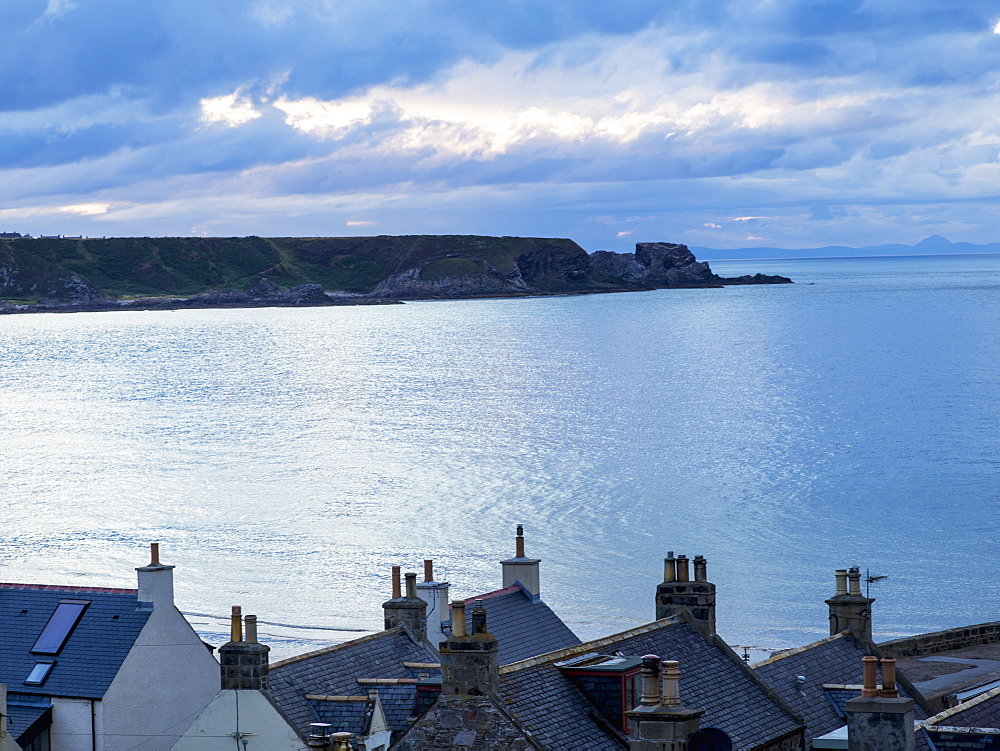 Cliffs Along The Coastline And Rooftops Of Houses In The Foreground, Cullen, Moray, Scotland