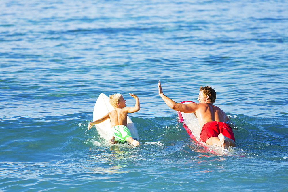 Happy Father And Young Son Going Surfing Together. Giving Each Other A Hi-Five!