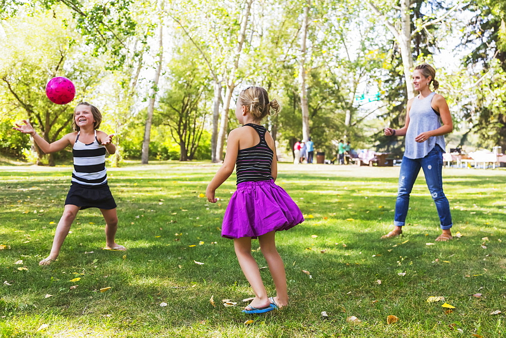 Mother And Daughters Throwing A Ball In A Park During A Family Outing, Edmonton, Alberta, Canada