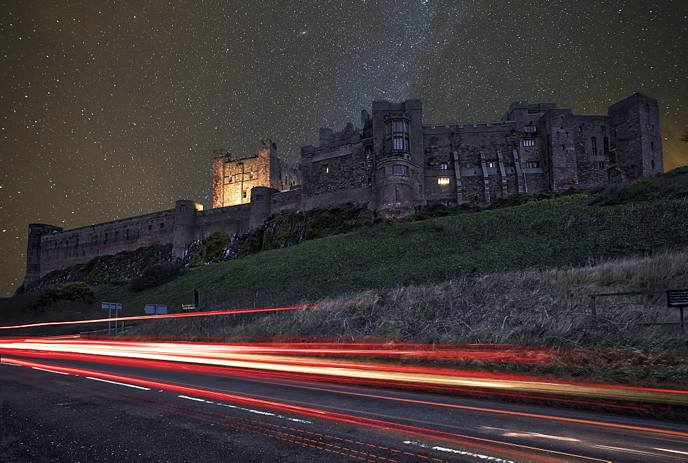 Light Trails On A Road And A Star Filled Sky Over Bamburgh Castle At Nighttime, Bamburgh, Northumberland, England