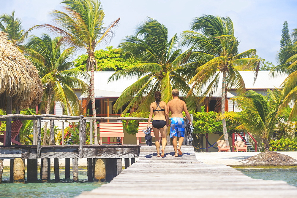 A Couple Walking On A Wooden Dock, Saint Georges Caye Resort, Belize City, Belize