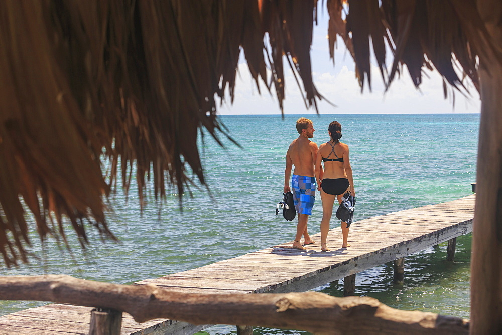 A Couple Walks On A Wooden Dock With Snorkelling Gear, Saint Georges Caye Resort, Belize City, Belize