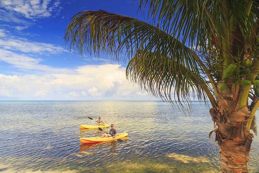 A Couple Using Kayaks At Saint Georges Caye Resort, Belize City, Belize