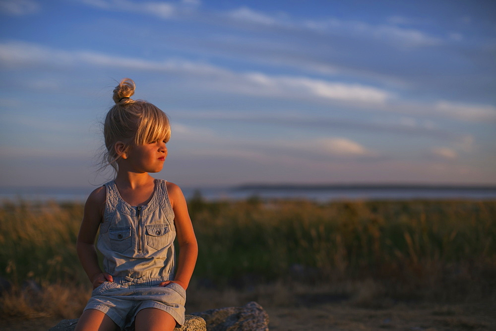 Portrait Of A Young Girl Sitting On A Rock On A Beach At Sunset, Surrey, British Columbia, Canada