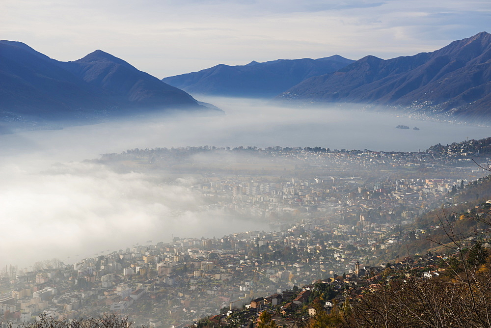 Fog Sets In Over A City And Alpine Lake, Locarno, Ticino, Switzerland