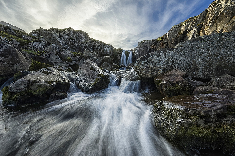 Stream Flows Over A Waterfall And Through The Rocks Along The Eastern Coast Of Iceland, Iceland