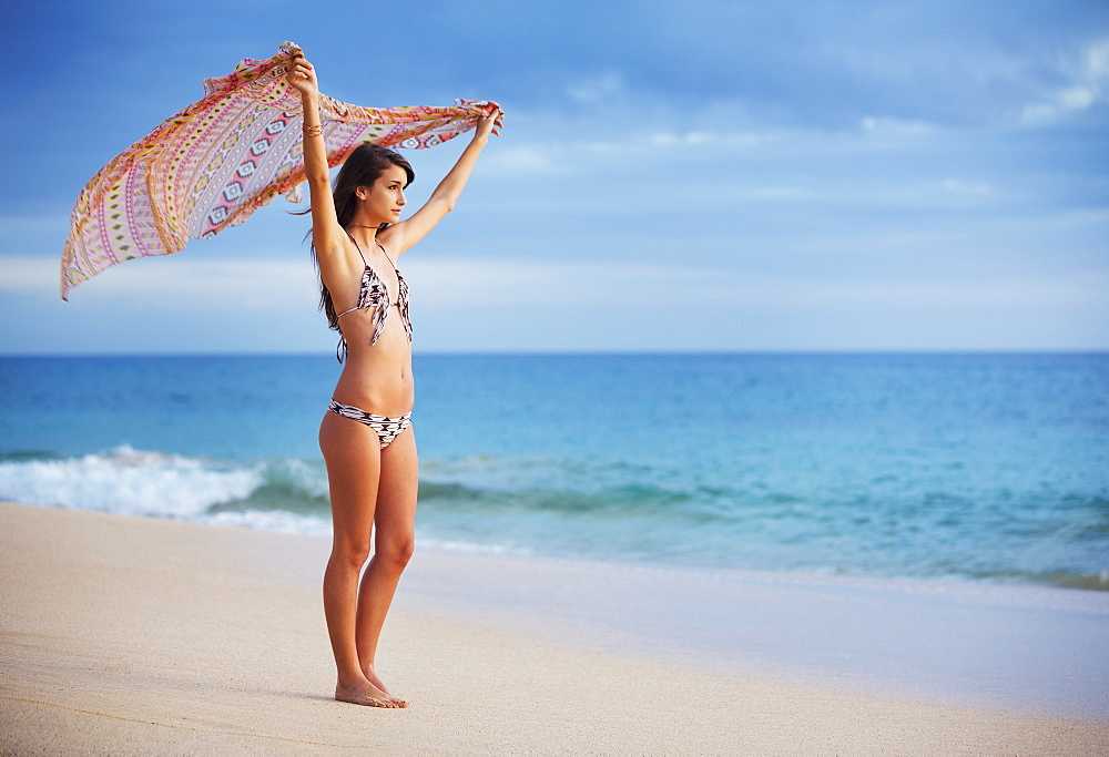 Beautiful Young Woman With Scarf On The Beach At Sunset. Travel And Vacation Concept. Fashion Lifestyle.
