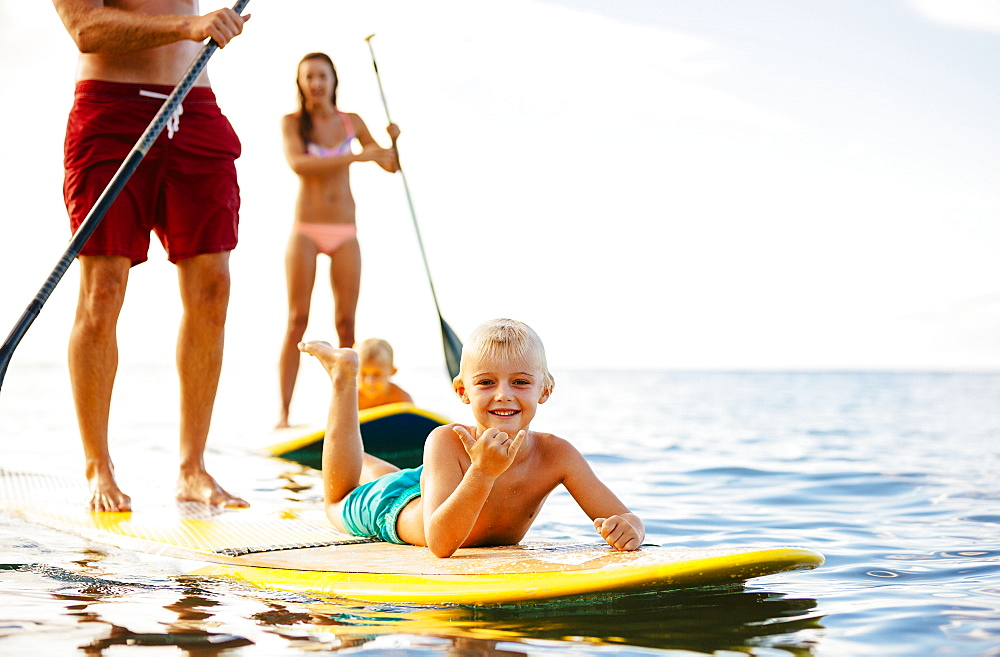 Family Having Fun Stand Up Paddling Together In The Ocean On Beautiful Sunny Morning