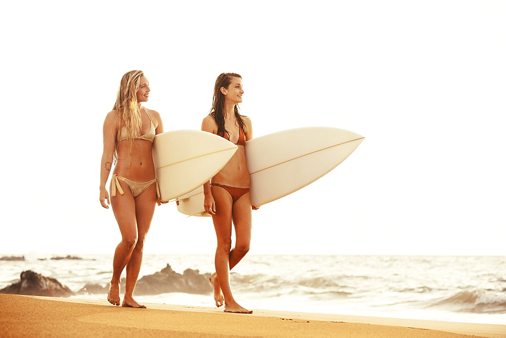 Beautiful Surfer Girls Walking On The Beach At Sunset