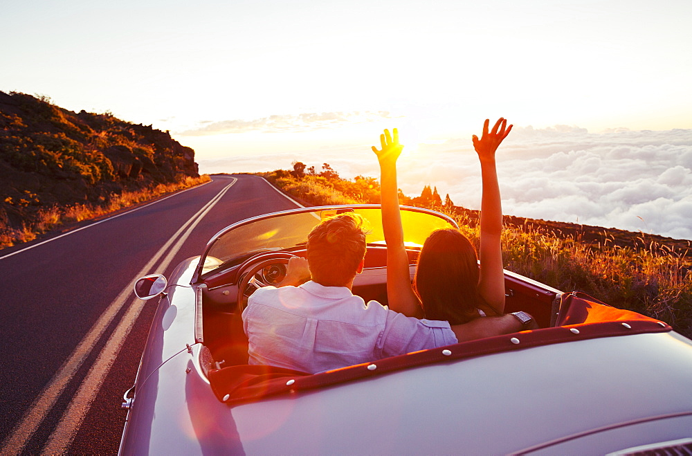 Driving Into The Sunset. Romantic Young Couple Enjoying Sunset Drive In Classic Vintage Sports Car