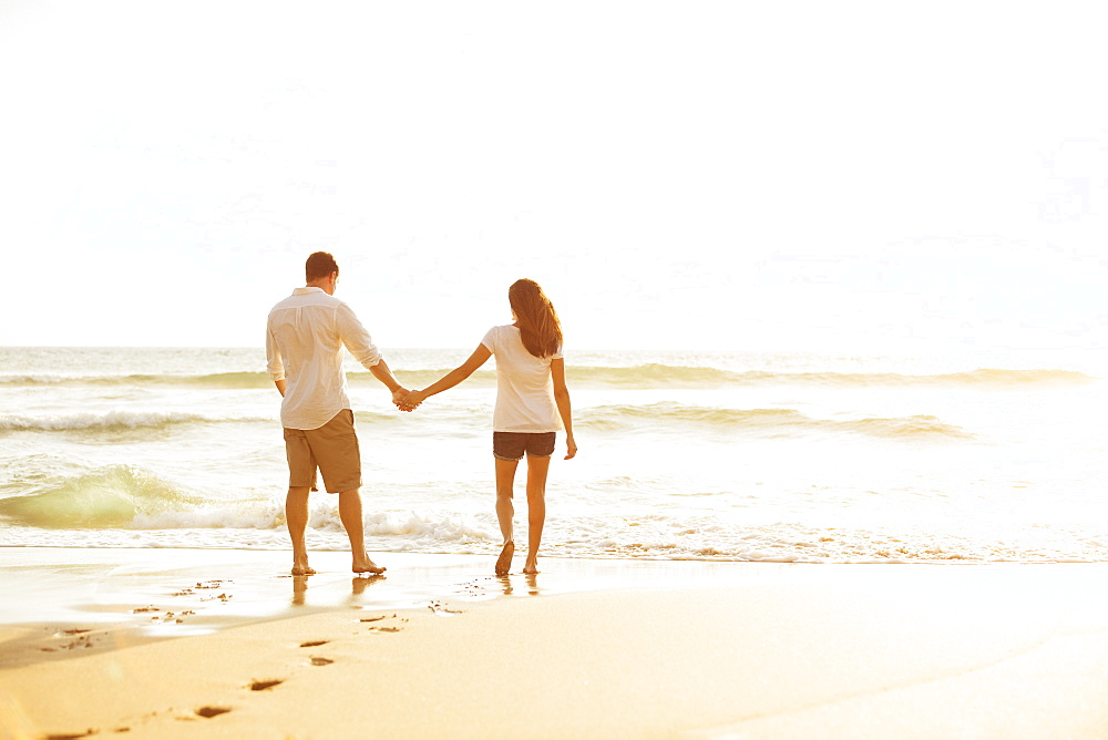 Happy Romantic Couple Walking On The Beach Enjoying The Sunset