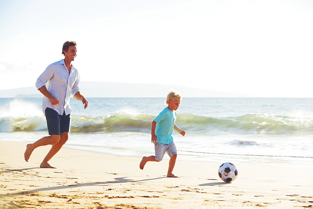 Happy Father And Son Having Fun Playing Soccer On The Beach