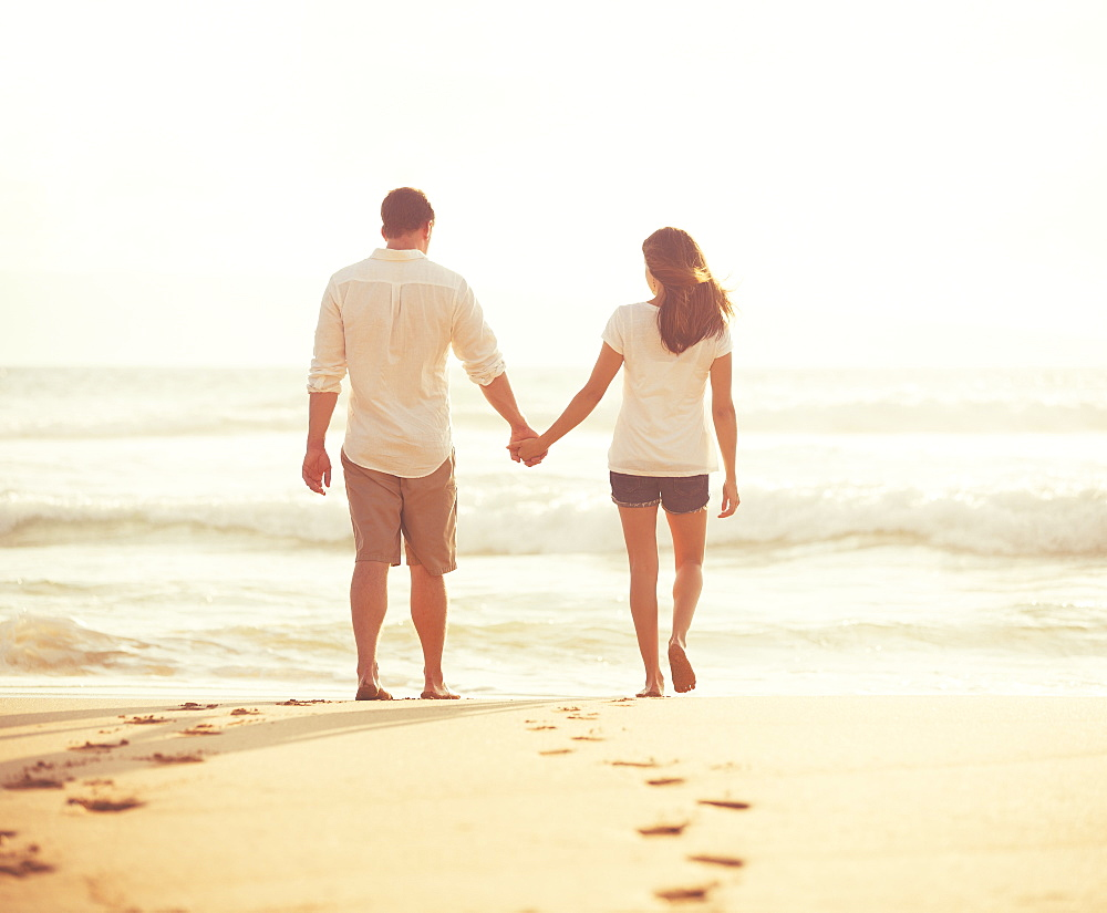 Romantic Young Lovers Walking Down The Beach At Sunset On Vacation
