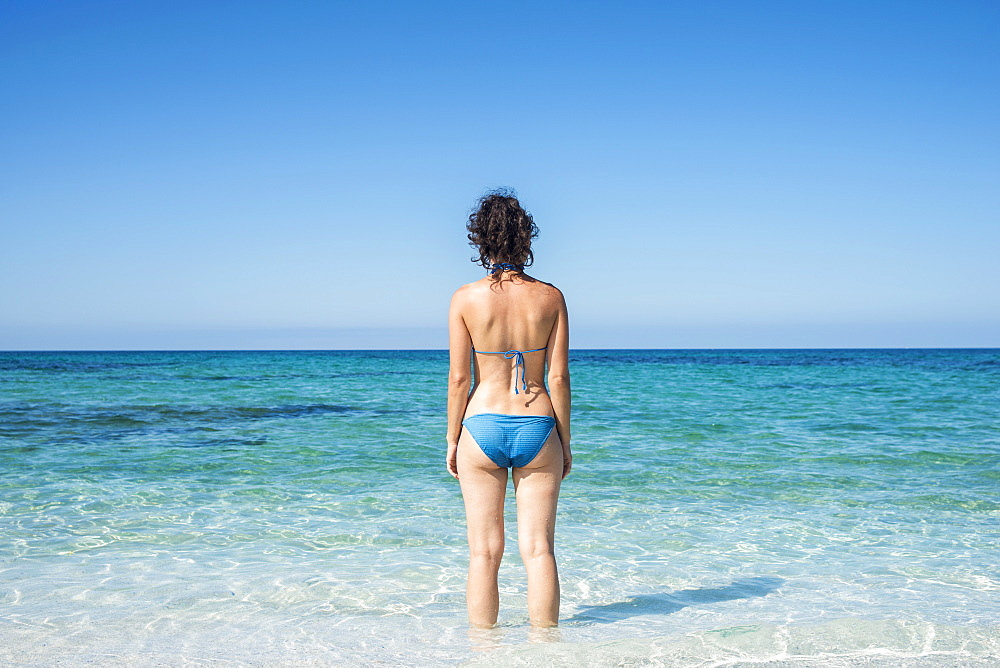Young Woman In A Blue Bikini At Mari Ermi Beach, Also Known As The Beach Of The Grains Of Rice, Oristano, Sardinia, Italy
