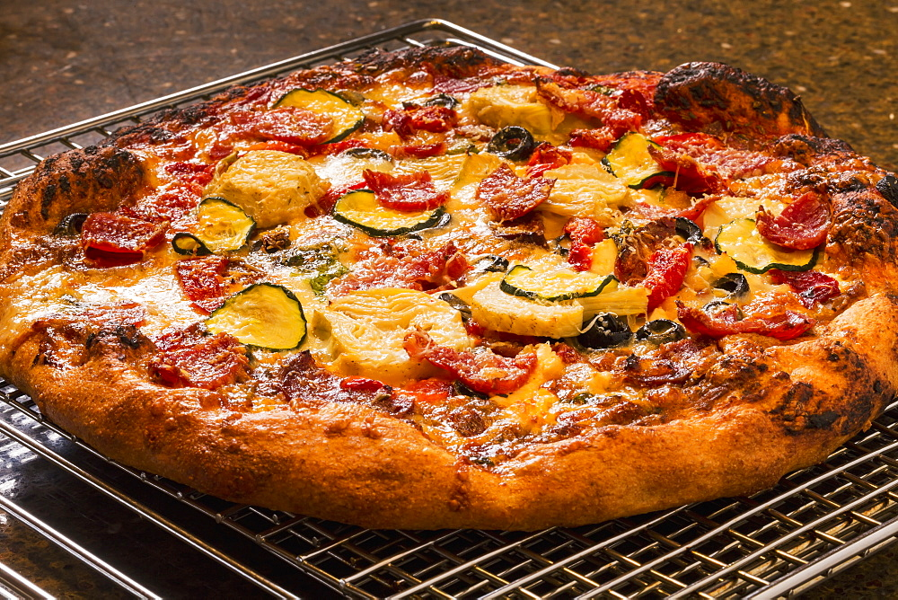 Close Up Of A Golden Crust Oven Baked Pizza On A Cooling Rack With Roasted Zucchini, Peppers, Artichokes, Mushrooms, Olives, Calgary, Alberta, Canada
