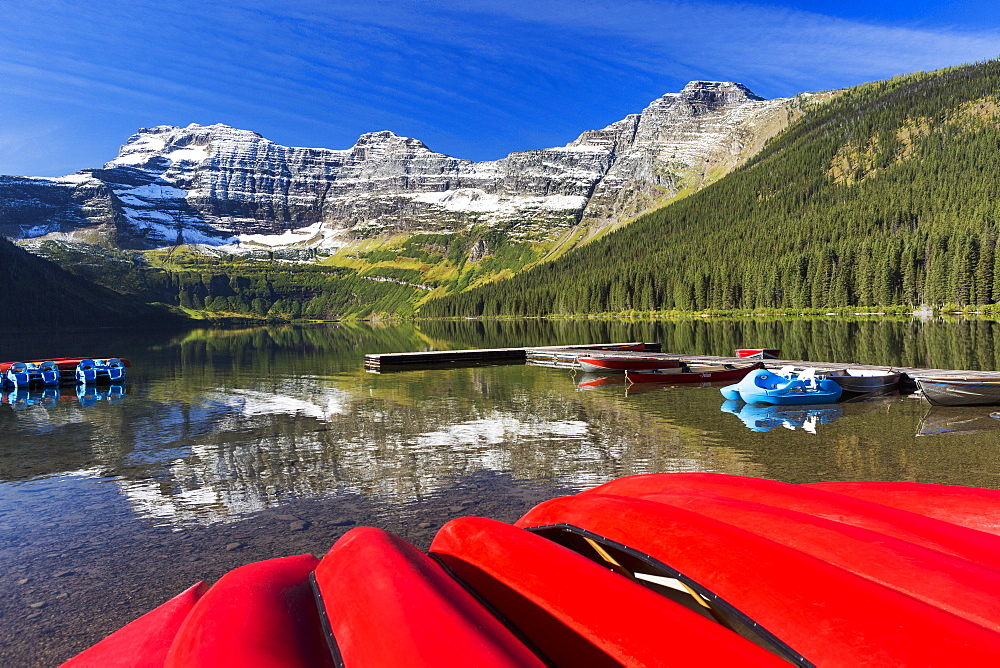 Mountain Lake With Dock Reflecting Snow Peaks And Blue Sky With Upside Down Red Canoes In The Foreground, Waterton, Alberta, Canada