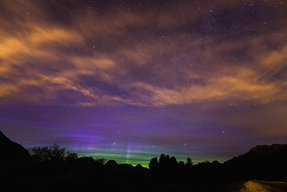 Stars And The Northern Lights (Aurora Borealis) Shine Through High Clouds Over Pitt Lake, British Columbia, Canada