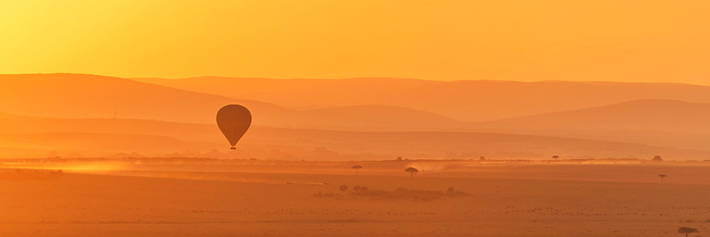 A Hot Air Balloon Flies Over The African Savannah In The Orange Light Before Sunrise, With A Trail Of Dust Below Made By A Truck On The Ground, Narok, Kenya