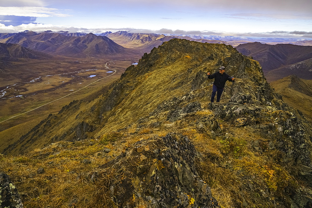 Man Hiking On A Lookout Overlooking The Blackstone Valley, Along The Dempster Highway, Yukon, Canada