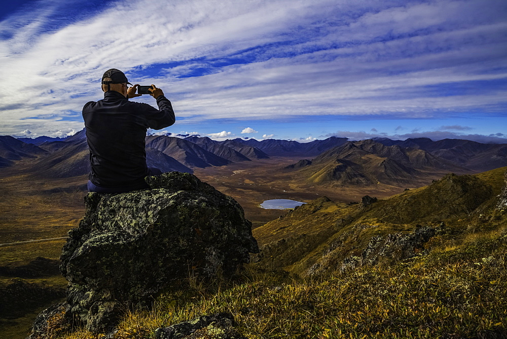 Man Using A Smart Phone To Take Photos On A Look Out Overlooking The Blackstone Valley, Along Dempster Highway, Yukon, Canada