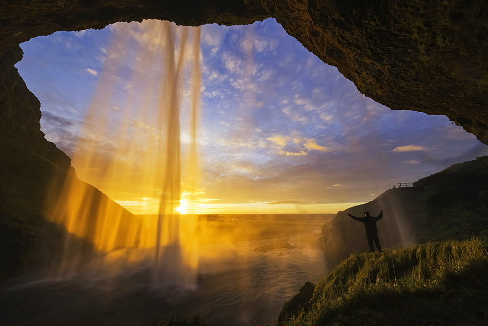 Man Standing Behind The Waterfall Known As Seljandafoss Along The Southern Coast Of Iceland, Iceland