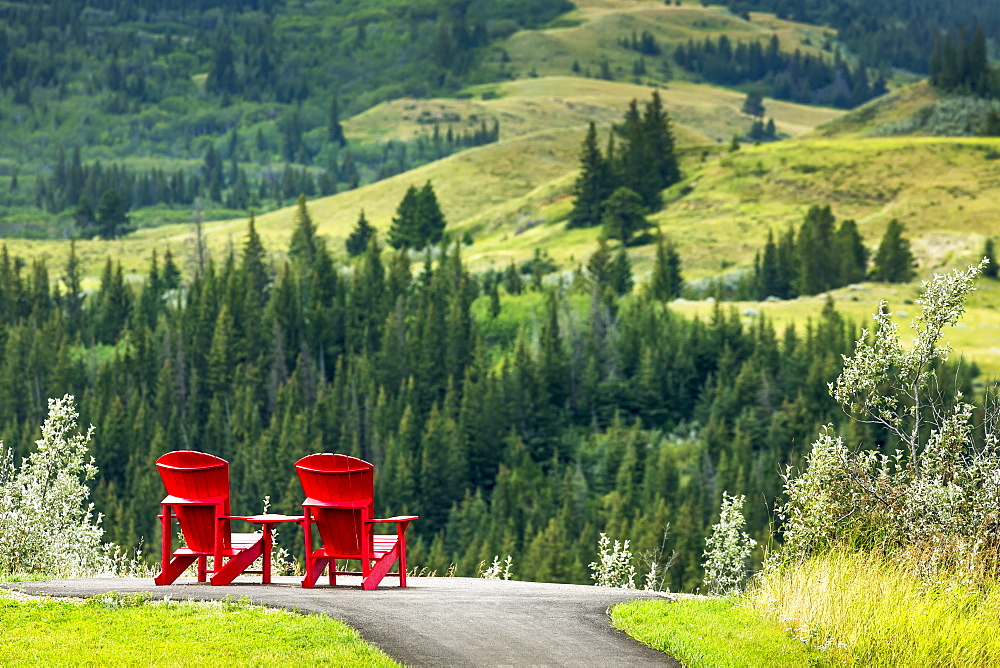 Two Red Adirondack Chairs On A Paved Pathway On Top Of A Hillside Overlooking Rolling Treed Hillside In The Distance, South Of Maple Creek, Alberta, Canada