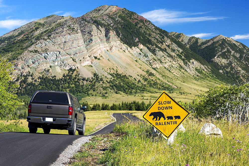 Cautionary Road Sign Of Bear Crossing On A Windy Mountain Road With Vehicle On Roadway, With Mountains And Blue Sky, Waterton, Alberta, Canada