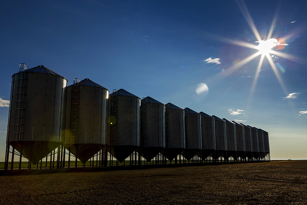 A Row Of Large Metal Grain Bins With A Sun Burst And Blue Sky, Mossleigh, Alberta, Canada