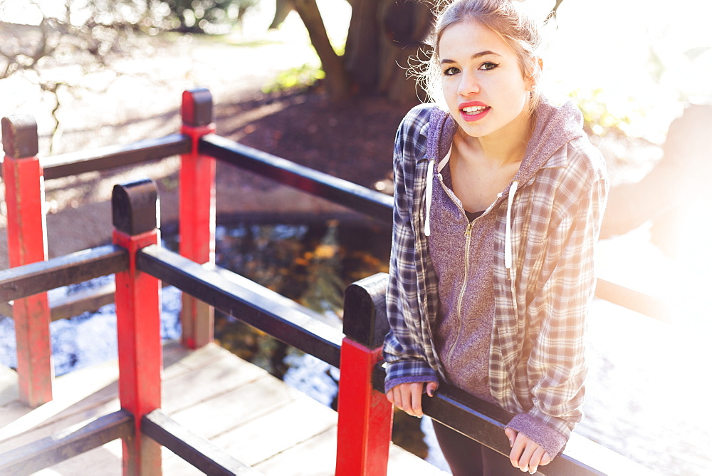 A Pretty Teenage Girl Makes A Playful Pose On A Boardwalk In The Park With Sunlight From Behind, New Westminster, British Columbia, Canada