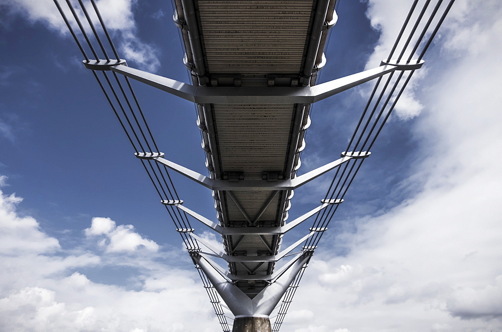 A Low Angle View Underneath The Millennium Bridge From The River Thames Bank In Bankside, London, England