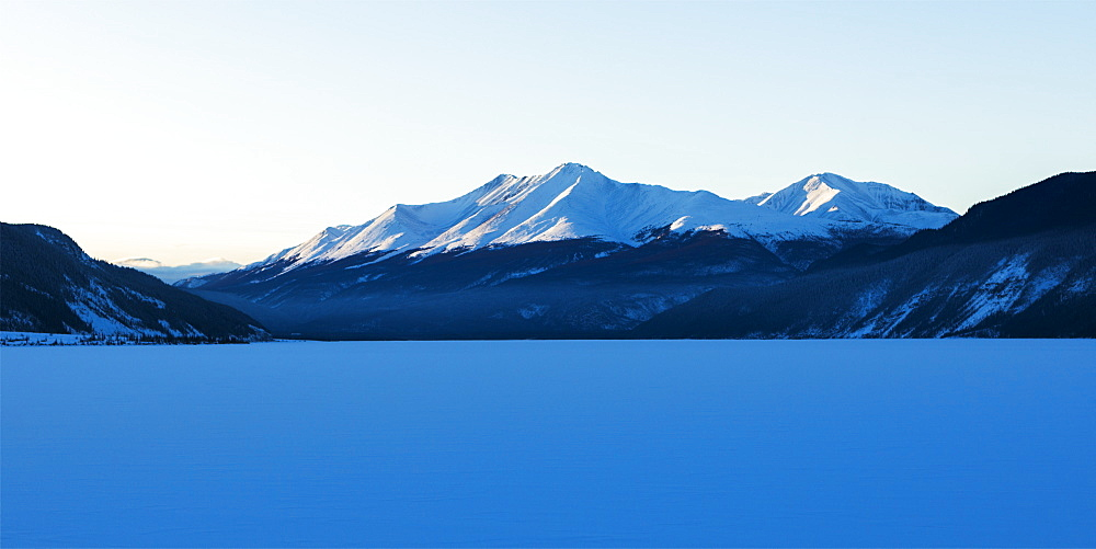 Frozen Snow Covered Lake With Snow Covered Mountains In The Background, Liard River Hot Springs Provincial Park, British Columbia, Canada