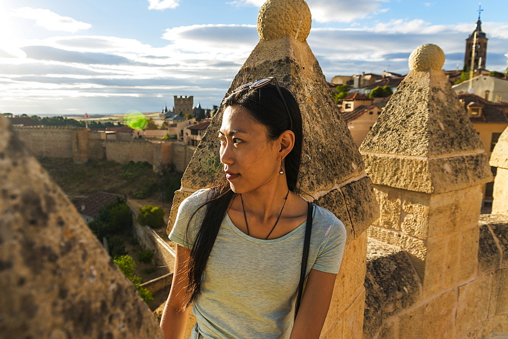 Asian Girl Sitting On The Ancient Walls Of Segovia, Segovia, Castilla Leon, Spain